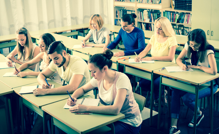 highschool students: Adult highschool students learning in classroom at their desks Stock Photo