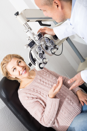 slit: smiling russian mature optician examinating eyesight with aid of slit lamp Stock Photo
