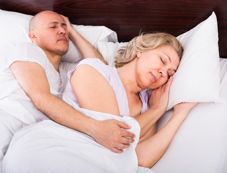 tight focus: Loving mature family couple sleeping tight in bed at night. Focus on woman