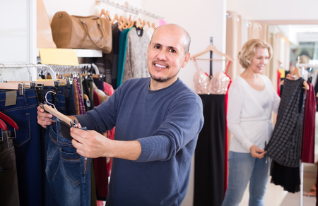 spouses: senior european spouses buying pair of classic jeans in boutique
