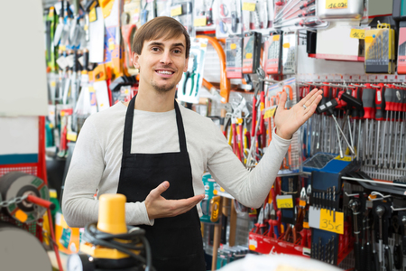 tooling: happy male seller posing at tooling section of household store