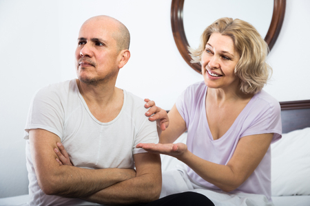 condone: Mature wife warmly comforting upset husband in bedroom
