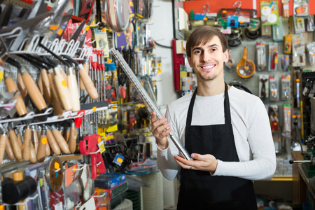 tooling: Young european male seller posing at tooling section of household store Stock Photo