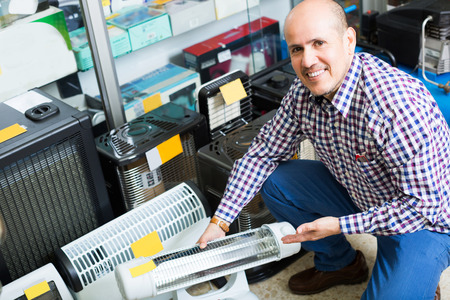 radiative: Mature male customer buying small heater in supermarket
