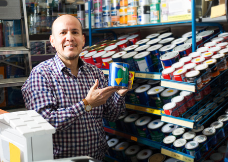 Smiling male pensioner choosing color of paint in supermarket Stock Photo