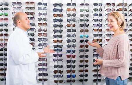 Professional male optician consulting mature female customer near sunglasses display Stock Photo