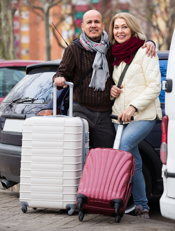 a two wheeled vehicle: Happy elderly spouses with luggage standing at street and smiling