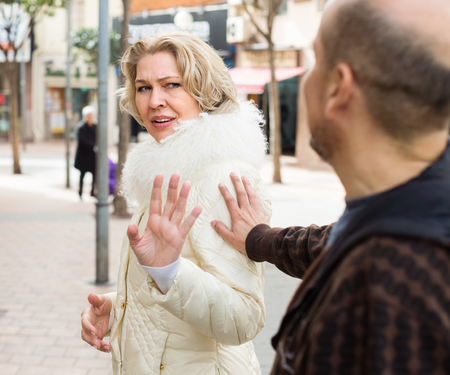 accosting: Impatient  old woman asking man not to bother her outdoor Stock Photo