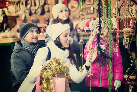 Family with children purchasing the Christmas decoration and the souvenirs at a fair. Focus on women