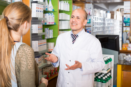 farmacy: Experienced senior pharmacist counseling female customer in modern farmacy Stock Photo