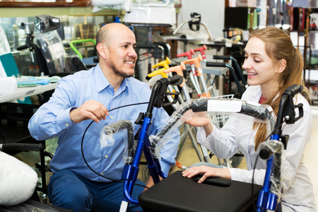 Young female consultant offering wheelchair to mature customer in orthopaedic store. Focus on the man Stock Photo