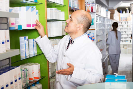 Friendly team of pharmaceutist and assistant working in chemist shop Stock Photo