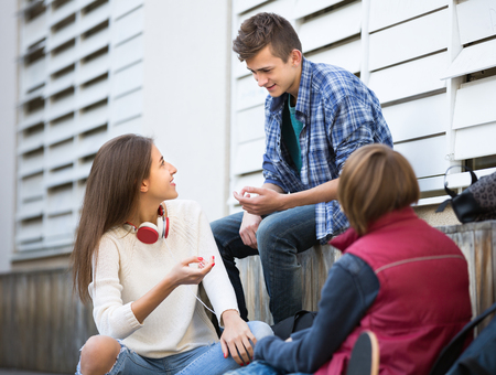 blabbing: Happy three teenagers hanging out outdoors and discussing something . Focus on girl