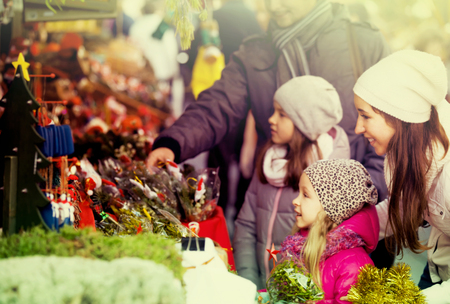 Family of four choosing x-mas decorations at market. Focus on woman