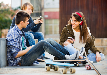16s: Smiling cheerful teens playing on smarthphones and listening to music