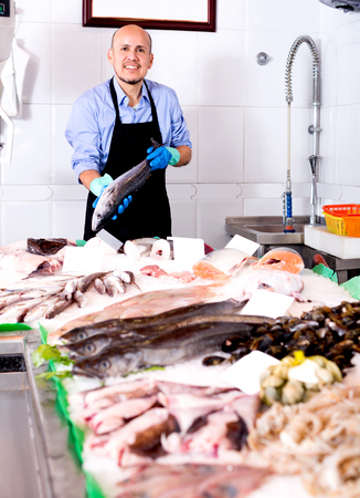 fish selling: Smile man selling chilled fish and seafood in store Stock Photo