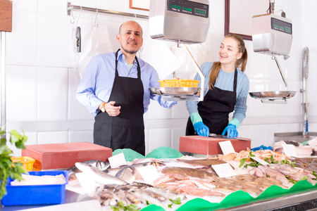 frozen fish: Young assistant and mature seller offering frozen fish in shop
