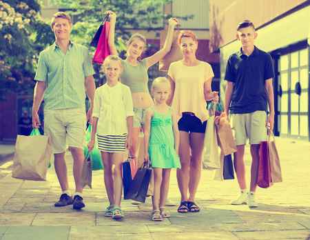 gladly: Smiling young parents with four kids gladly shopping in town