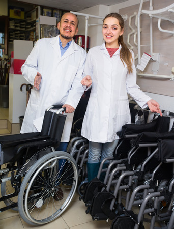 Two consultants in white overalls selling wheelchairs in special store with orthopaedic goods