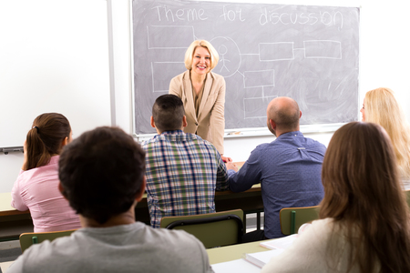 attentive: Teacher standing in class in front of attentive mixed age students