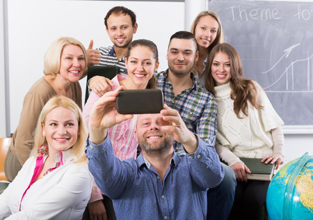 normal school: russian students of different age doing group selfie on smartphone Stock Photo