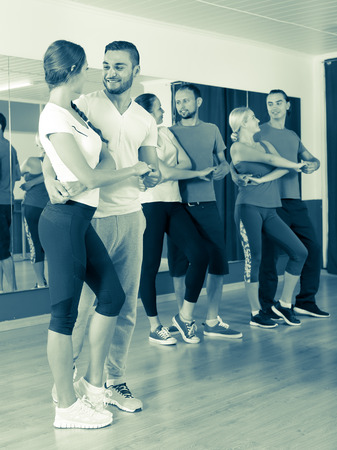 unprofessional: Smiling adults dancing the bachata together at the dance studio