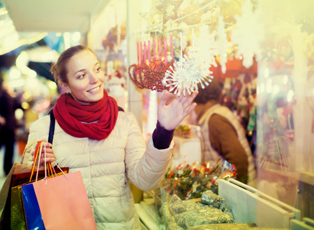 spanish woman: Beautiful young spanish woman choosing Christmas decoration at market in evening time