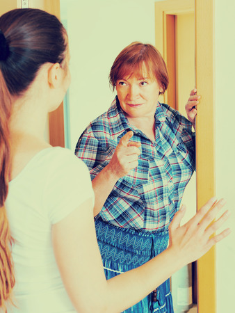 Mature woman dissatisfied mother meet her young daughter at home Stock Photo