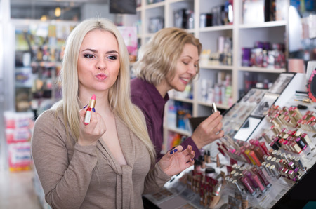 beauty store: Portrait of two cheerful women selecting lipstick in beauty store
