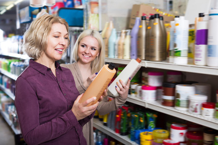 Adult women chooses shampoo in cosmetic store Stock Photo