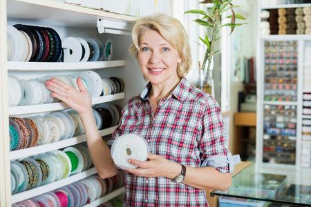 elastic band: Glad woman customer buying ribbon or elastic band in sewing store