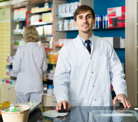farmacy: Portrait of positive young spanish  male pharmacists working in modern farmacy