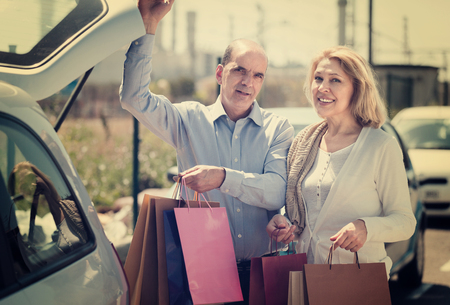 Smiling elderly couple putting bags with purchases in trunk Stock Photo