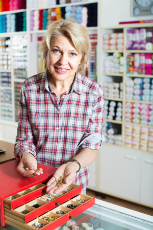 clasps: mature smiling woman customer choosing various metallic clasps in sewing store counter