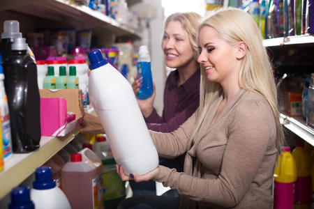 vend: Two positive women choosing some detergents in supermarket