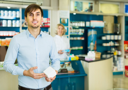 smiling american handsome man   in pharmacy drugstore Stock Photo