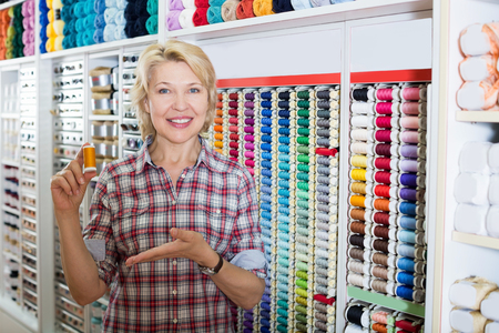 glad: Glad mature woman holding stitching spool in sewing departament at store