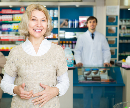 Mature woman near counter in pharmacy drugstore Stock Photo