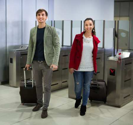 baffle: Passengers with a luggage passing the turnstile at metro station. Focus on man