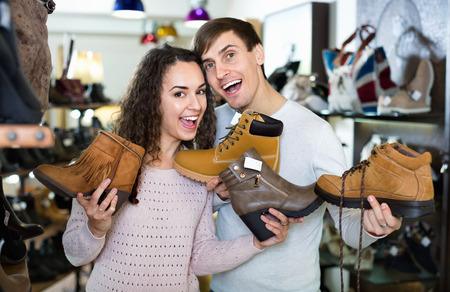 comprando zapatos: Smiling happy young couple buying winter shoes in a shoe store