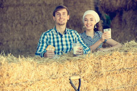 smiling young man and woman chatting and enjoying fresh milk in the hay Stock Photo