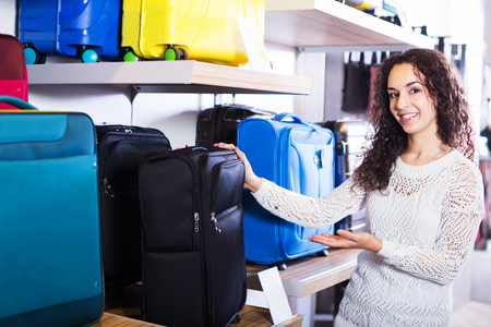 haberdashery: Young positive woman selecting travel suitcase in haberdashery shop Stock Photo