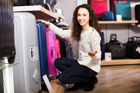 haberdashery: Young positive woman choosing travel suitcase in haberdashery shop