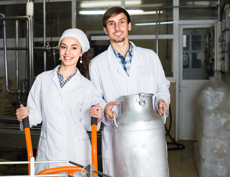 lab coats: ?Portrait of young man and woman dressed in lab coats working on the dairy laboratory
