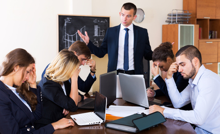 Disappointed young boss shouting at employees in office interior. Focus on the left woman