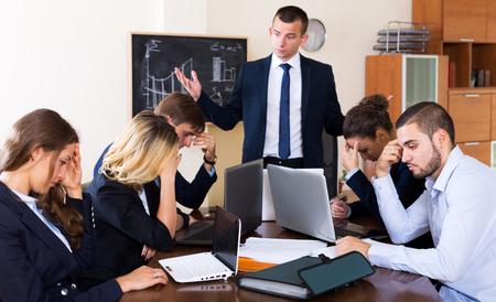 Teleurgestelde jonge baas schreeuwen naar medewerkers in het kantoor inter. Focus op de linker vrouw Stockfoto