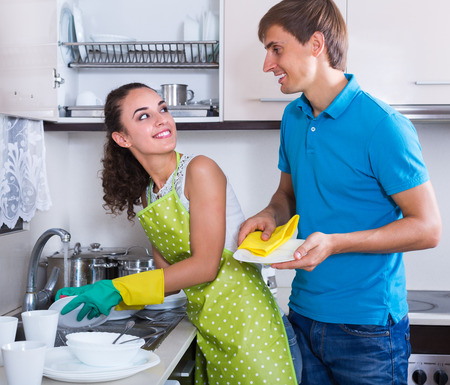 Young spouses doing regular laundry indoors
