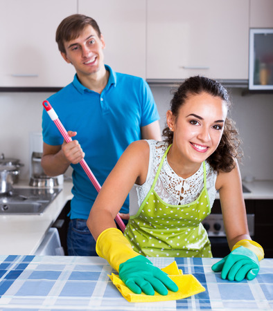 dusting: Young man mopping and smiling woman dusting in domestic kitchen