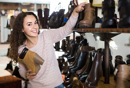 comprando zapatos: adult female buying winter female shoes in  shoe store