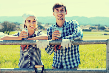 russian man: smiling young russian man and woman chatting and enjoying milk outdoors Stock Photo